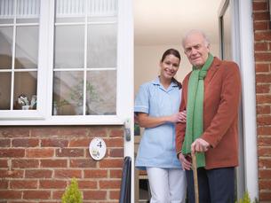 Nurse and older man standing in doorwayの写真素材 [FYI03496190]