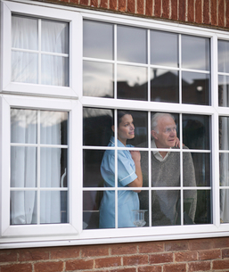 Nurse and older man at windowの写真素材 [FYI03496193]