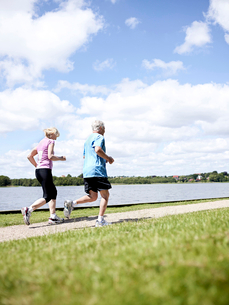 Older couple jogging together outdoorsの写真素材 [FYI03496245]