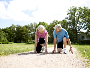 Older couple crouched in start positionの写真素材 [FYI03496247]