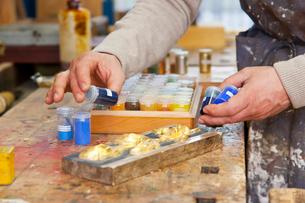 Carpenter examining jars of pigmentの写真素材 [FYI03496291]