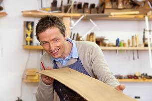 Carpenter examining sheet of woodの写真素材 [FYI03496292]