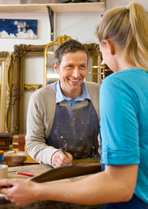 Carpenter talking to woman in shopの写真素材 [FYI03496293]