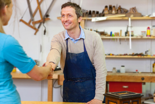 Carpenter shaking hands with clientの写真素材 [FYI03496298]