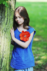 Girl leaning against tree in parkの写真素材 [FYI03496306]