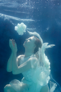 Woman swimming in ornate gownの写真素材 [FYI03496316]