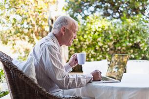Older man using laptop outdoorsの写真素材 [FYI03496398]