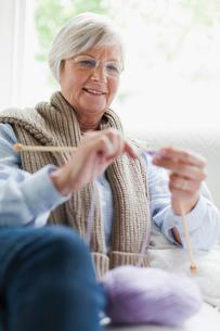 Smiling older woman knittingの写真素材 [FYI03496419]