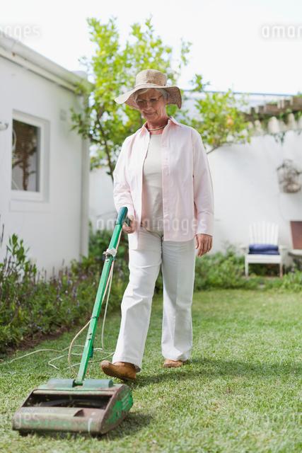 Older woman mowing lawn in backyardの写真素材 [FYI03496429]