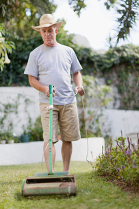 Older man mowing lawn in backyardの写真素材 [FYI03496430]