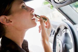 Woman applying lipstick in car mirrorの写真素材 [FYI03496443]