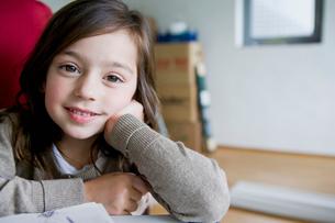 Smiling girl sitting at deskの写真素材 [FYI03496466]