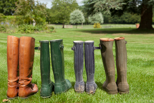 Pairs of boots standing in fieldの写真素材 [FYI03496639]