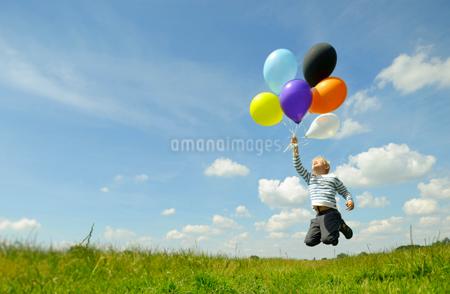 Boy playing with balloons in meadowの写真素材 [FYI03496704]