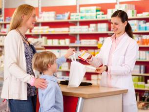 Pharmacist filling prescription in storeの写真素材 [FYI03496823]