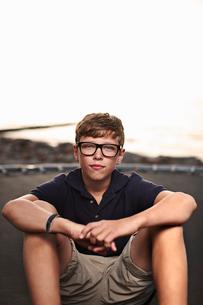 Teenage boy sitting on trampolineの写真素材 [FYI03496863]