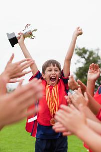 Children cheering teammate with trophyの写真素材 [FYI03496984]