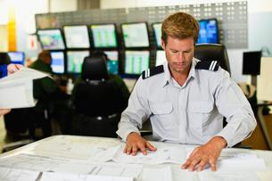 Man working in security control roomの写真素材 [FYI03496993]