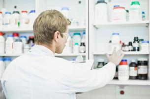 Scientist examining jars in labの写真素材 [FYI03496998]