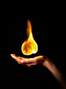 Hand holding burning flameの写真素材 [FYI03497137]