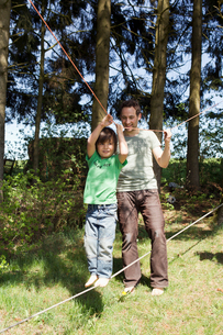 Father helping son walk on tight ropeの写真素材 [FYI03497265]