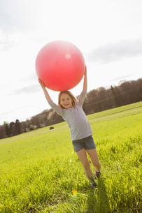 Girl carrying bouncy ball in fieldの写真素材 [FYI03497305]