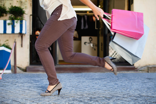 Woman running with shopping bagsの写真素材 [FYI03497434]
