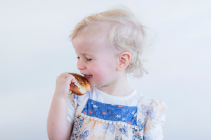 Toddler girl eating pastry indoorsの写真素材 [FYI03497453]