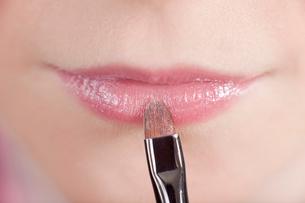 Close up of girl applying makeupの写真素材 [FYI03497616]