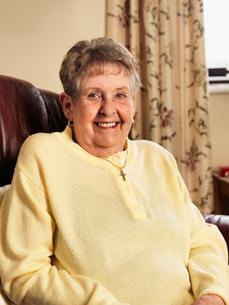 Smiling older woman sitting in armchairの写真素材 [FYI03497630]