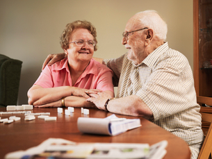 Older couple playing dominoes togetherの写真素材 [FYI03497633]