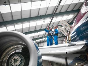 Workers examining airplane in hangarの写真素材 [FYI03497834]