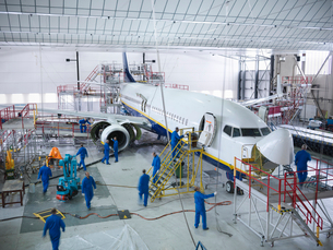 Workers in airplane hangarの写真素材 [FYI03497860]