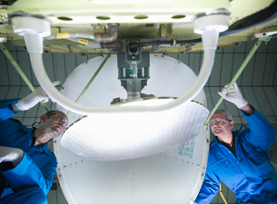 Workers fitting nose to airplaneの写真素材 [FYI03497866]