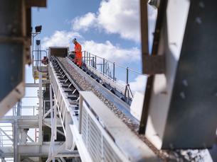Worker examining stones on conveyor beltの写真素材 [FYI03497872]