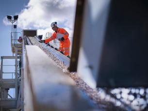 Worker examining stones on conveyor beltの写真素材 [FYI03497873]