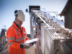 Worker with clipboard by conveyor beltの写真素材 [FYI03497877]