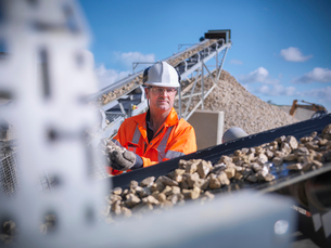 Worker examining stones on conveyor beltの写真素材 [FYI03497878]