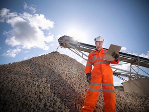 Worker standing by pile of stonesの写真素材 [FYI03497880]