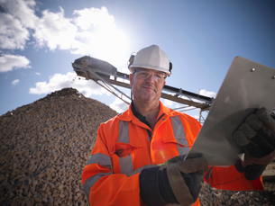 Worker standing by pile of stonesの写真素材 [FYI03497881]