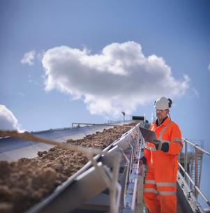 Worker with clipboard by conveyor beltの写真素材 [FYI03497882]