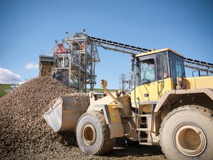 Digger scooping pile of stones in quarryの写真素材 [FYI03497885]