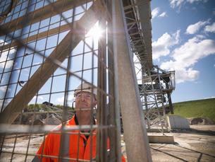 Worker standing under conveyor in quarryの写真素材 [FYI03497888]
