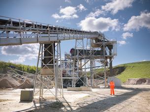 Worker standing by conveyor in quarryの写真素材 [FYI03497889]