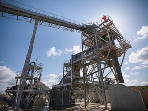 Worker standing on conveyor in quarryの写真素材 [FYI03497890]