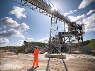 Worker standing under conveyor in quarryの写真素材 [FYI03497891]