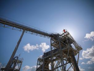 Worker standing on conveyor in quarryの写真素材 [FYI03497892]