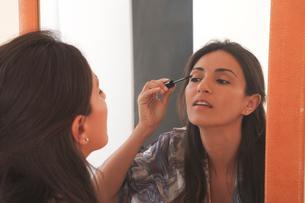 Woman applying makeup in mirrorの写真素材 [FYI03498171]