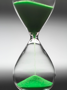 Green sand pouring through hourglassの写真素材 [FYI03498479]