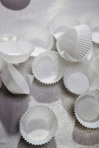 Cupcake wrappers and flour on tableの写真素材 [FYI03498502]